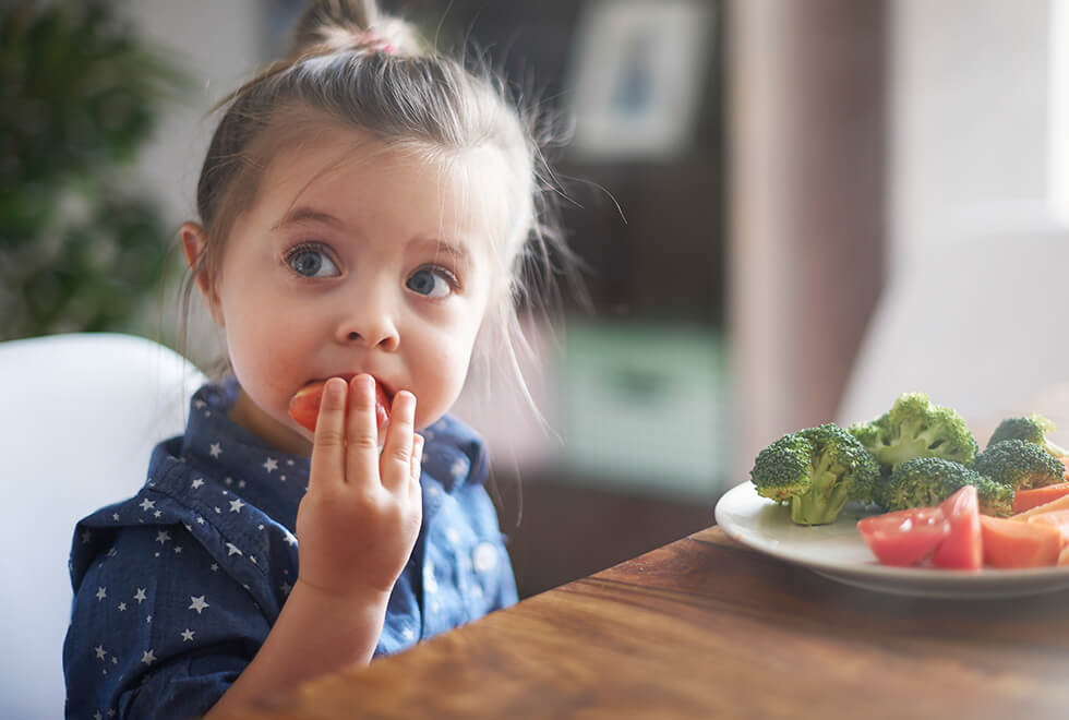 Toddler eating tomato from a plate